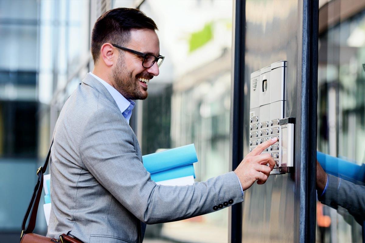 businessman-pressing-intercom-system