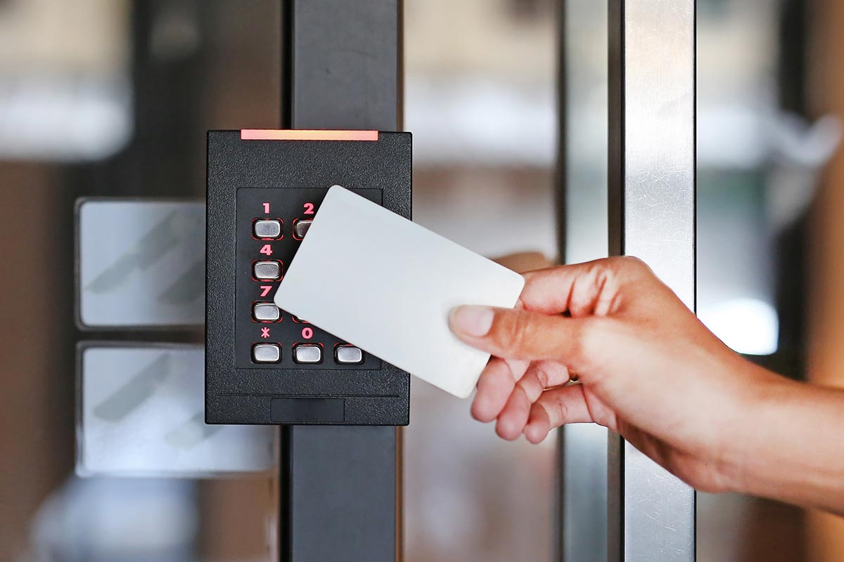 hand-holding-access-card-up-to-security-keypad